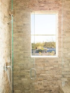 With a rich dark wood vanity and an enticing walk-in shower that features beautiful stacked stone walls, the guest bathroom reflects the earthy materials and authentic style of this desert modern home.