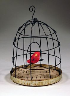 bird in a cage, love the sheet music lining the bottom of the cage.