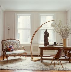 In the living room the graceful Arc floor lamp was found in Paris and illuminates a sturdy table displaying an antique sculpture and large vase containing a simple arrangement of flowering branches