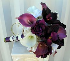 """This Wedding bouquet has class and elegance. Real touch calla lilies & orchids are soft to touch and look so real, you are sure to love them. Bouquet is designed with 10 eggplant purple & white calla lilies, 3 plum orchids, creamy white hydrangea, & plum delphinium, framed with curly willow loops and grass. Handle treatment is wrapped with a plum satin overlay ribbon and a white satin sash ribbon, completed with a sparkling rhinestone buckle. Bouquet measures: 10"""" ( 23 cm ) wide x 12"""" ( 30…"""
