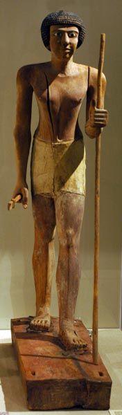 Wepwawet-em-hat, Museo de Bellas Artes de Boston. Primer Período Intermedio. Din X-XI.   En estos momentos nace una creatividad propia que se aleja de las normas del Reino Antiguo. Las imágenes serán más toscas y de menor calidad, pero ganan en realismo, vitalidad y originalidad. Las imágenes exentas son pocas, se sustituye la piedra por madera como en la figura de Wepwawet, de ojos expresivos y mirada fija, donde se ve la destreza en el modelado del cuerpo y largos dedos de la mano.