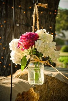 Mason jar hanging from Shepherds hooks.  Buy flowers from Sams and make up arrangements the day before.
