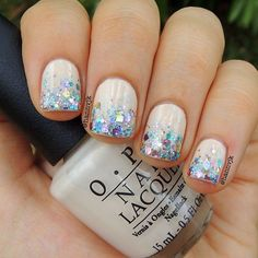 nude polish with multi color glitter tips.
