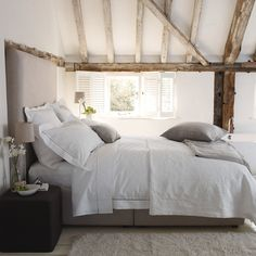 heavenly bedroom in the eves with ancient beams, white wooden shutters and contemporary linen high headboard - The Paper Mulberry: White