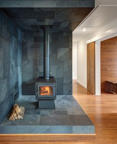 Vermont slate covers the area around the True North wood stove. Wide-plank Yanachi Carbonized Strand Woven Bamboo covers the floors. Photo by: Greg Clark Wood Stove Surround, Wood Stove Hearth, Slate Fireplace, Fireplace Ideas, Wood Burner, Modern Fireplace, Fireplace Mantels, Arkansas, Pellet Stove