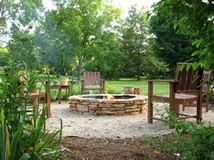 Round fire pit with seating and landscaping.  Grab a drink and have a seat!