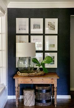 love this dark accent wall + the way the photos are displayed - lovely art wall