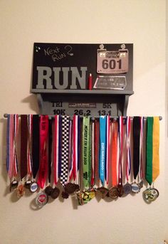 Runner's Medal Display / holder - spray painted regular book shelf & a rod from craft store, bought a thin metal/chalkboard. Painted #'s and letters, glued them along with a favorite running quote to the shelf. Magnets hold running # - this was a surprise gift for the runner who use to keep his medals on a hanger in the closet