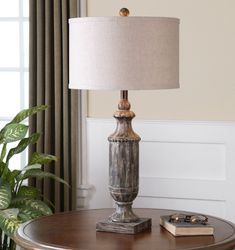 Agliano Table Lamp Uttermost in Table, Desk and Buffet Lamps. Aged dark pecan stain with a burnished wash and off-white paint drips. The round hardback drum shade is an oatmeal linen fabric with natural slubbing. Table Lamp Wood, White Table Lamp, Table Lamp Sets, Light Table, Desk Lamp, Rustic Table Lamps, Off White Paints, Aging Wood, Drip Painting