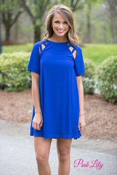 This gorgeous little dress will help you break the ice at any party - everyone will be asking where you found it! It features a series of unique cutouts and straps on each shoulder, a royal blue fabric and chiffon overlay, and comfortable fabric that will stay cool all day long. It also has a zipper in back and short sleeves.
