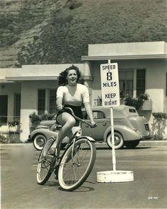 Anne Gwynne rides a bike.
