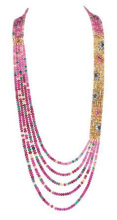serti de boules de rubellites et de tourmalines, de saphirs jaunes et d'émeraudes et de grenats spéssartites, pavé de rubis, d'émeraudes, de saphirs jaunes et roses et de diamants, sur or jaune. Un motif de 8,5 cm est placé de chaque côté du collier et se détache pour être assemblé en un bracelet. Le collier peut ainsi être porté plus court.