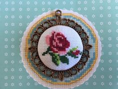 Handmade elegant cross stitch necklace with detailed rose pattern. The pendant features a hand made cross stitch design in different shades of pink,red and green sitting in a metal frame setting. Pendant measures 6 cm / 2.36 inch Silver plated chain measures approximately 82 cm / 32.28