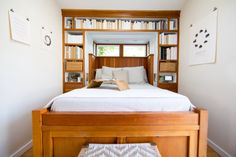 """The tiny bedroom is our favorite part of the cottage. There is ample storage below the built-in bed, and we love the beautiful bookshelves and windows."""