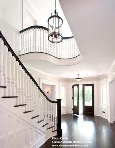 Railing Idea Grand formal foyer with dark hardwood floors and double front doors. Sweeping paneled staircase with white spindles and dark handrail. Curved balcony overlooking stairs, white walls and large glass and iron pendant. Floor Stain Colors, House Design, Foyer Decorating, Future House, Home, Hardwood Floors Dark, House Goals, House, New Homes
