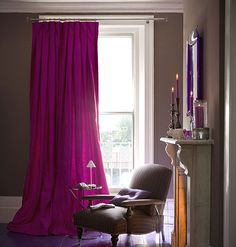 Curtains that puddle on the floor emphasize the opulence of a space. These pink silk draperies give a luxe look to this simple arm chair.