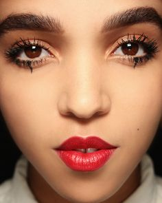 FKA Twigs with bold brows, rich red lips, minimal lids.