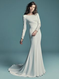 Maggie Sottero - OLYSSIA, This elegant sleeved wedding dress is comprised of Talin Stretch Crepe. Featuring a bateau neckline, scoop back, and lace illusion along the long sleeves. Finished with covered and crystal buttons over zipper closure. Detachable overskirt accented in lace sold separately. Maggie Sottero Wedding Dresses, Modest Wedding Dresses, Designer Wedding Dresses, Bridal Dresses, Wedding Gowns, Prom Dresses, How To Dress For A Wedding, Long Sleeve Wedding, Wedding Dress Sleeves