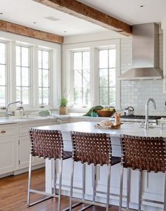 White kitchen with large windows and wood ceiling beams   Wettling Architects