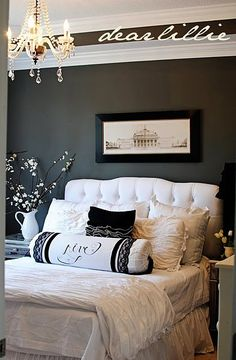 Love this sumptuous bedding and headboard, dark grey wall, and chandelier