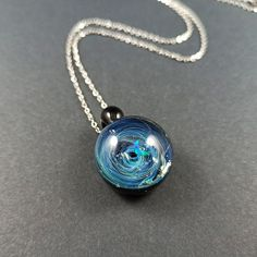 Glass galaxy pendant made with Silver fumed Borosilicate, with a floating green crescent moon opal, handblown glass galaxy pendant