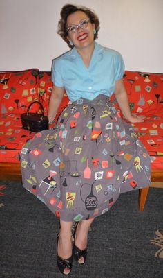Great examples of atomic bark cloth on her sofa and skirt.  Just love it!