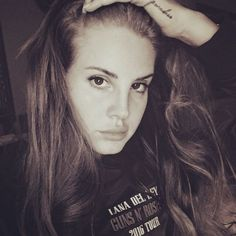 """Lana Del Rey's black-and-white Coachella photo is turning heads — thanks to her awesome shirt that reads """"Lana Del Rey Guns N' Roses 2016 Tour."""" How do we get tickets? ..."""