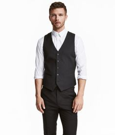 Black. Suit vest in woven fabric with back section in lining fabric. Chest pocket, welt front pockets, and buttons at front. Adjustable tab at back. Lined.