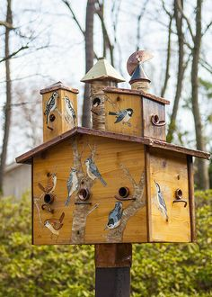 .birdhouse decorated with painted birds. t