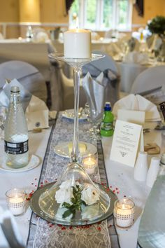 A lovely upside down Martini glass set up as a centrepiece. With a white candle at the top and 3 white roses at the bottom.