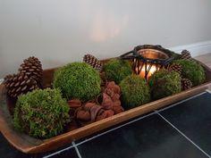Oude houten trog gevuld met mosbollen, dennenappels en kaars voor extra sfeer!