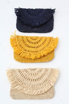 "Crocheted raffia clutch bags, lined with magnetic snap. In ocher, natural or navy. Aprox. 7 1/2"" x 6"" Made by hand using natural materials sourced sustainably from Madagascar's precious forests. The s"