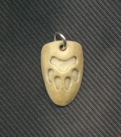 Wolf Pawprint Pendant X1 ~  carved fossil walrus ivory, about one inch high.  Artist  *DonSimpson on deviantART