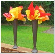 Fab Olympic torch centerpieces made from tall plastic glasses from the Dollar Tree, spray paint, and tissue paper.
