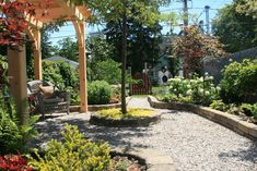 This former parking lot has been converted into a restful retreat. The timber frame post-and-beam construction by Okewood Timberworks is repeated in the garden's pergola. The homeowners laid the stone border donated by a friend, installed the pebble path and planted the trees, shrubbery and flowers.