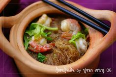 Seasoned mungbean noodles with shrimp in a clay pot.