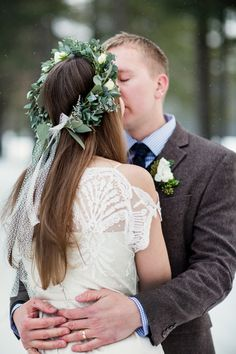 The bride wears a stunning off the shoulder, short sleeve, lace boho wedding dress and eucalyptus flower crown at a winter wedding at Lake Placid Lodge