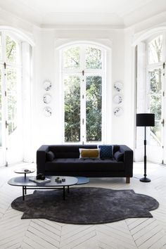 "#1White Space!  Towering ""bay"" window/door walls, view, white wood floor.  Replace rug with Sisal, light neutral tone on tone or Persian.  Replace black sofa upholstery with grey, beige, linen and or white."