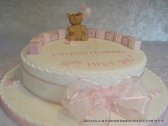 Elegant white round christening cake decorated with simple pink and white flowers and topped with a handmade sugar modelled teddy bear and building blocks spelling the childs name. Finished off with a pink chiffon ribbon and large tied bow