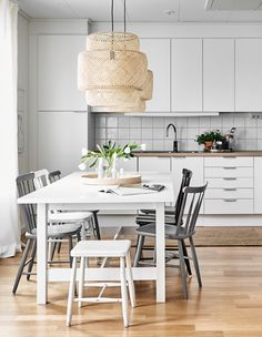 Kuchnia w bieli i neutralnych kolorach z dużym kuchennym stołem i krzesłami, ozdobiona prostym bukietem kwiatów.