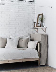 En sammenbrettet madrass med hjemmelaget trekk plassert mellom ei seng og en vegg.