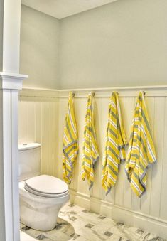 gray and yellow bathroom with grayblue walls over white tongue and groove wainscoting from which four yellow gray and white striped towels hang from wall