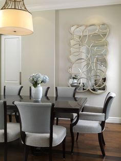 Understated beauty with a Dressmakers chandelier suspended over Barbara Berry for Baker table and chairs covered in Kravet fabric. The carved mirror is by Christopher Guy adds a contemporary touch. Modern Dining Room Design