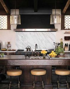 Michael Smith traditional and modern blend in the kitchen. Venetian-style windows let in light while preserving privacy. Stools by Paul Ferrante. Word Pendants by Alison Berger.