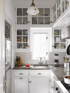 """Don't: Have cabinets that fall short of the ceiling. """"They collect dust and un-needed accessories,"""" designer Joan Schindler says. In this Connecticut kitchen, cabinets are full height and create the maximum amount of storage, while glass fronts keep the space feeling airy. The panes are restoration glass, which is uneven. The cabinets are painted Decorators White in semigloss by Benjamin Moore."""