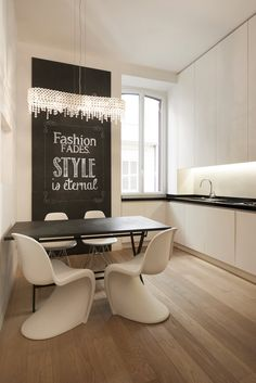 The kitchen is custom made and characterized by the two colors, black and white. A frontal wall covered by a blackboard covering, creates a sharing space dedicated to the entire family. Rome, Italy. Z Apartment by Carola Vannini | HomeAdore
