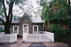 stone-front cottage with white picket fence <3