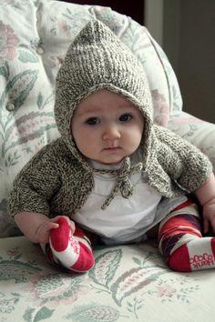 hilarious baby models the Elizabeth ZImmerman baby surprise jacket.