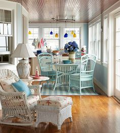 Cozy cottage porch filled with wicker accessories, flowers and soft bright colors