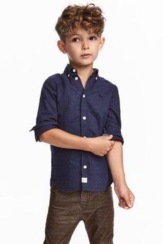 Pamuklu dokuma kumaştan, uzun kollu, yakası ve önü düğmeli gömlek.